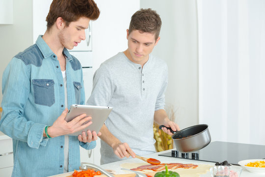 2 young men cooking together at home