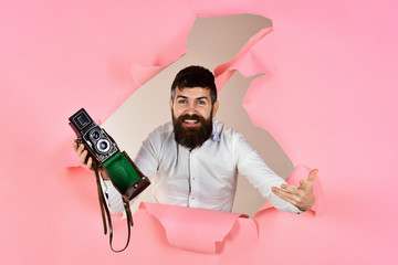 Handsome man with vintage photo camera. Bearded man holds vintage camera looking through hole in paper. Photography, technology concept. Photographer with retro film photo camera. Retro photocamera.