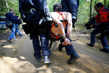"A naked female activist is carried away by police after being arrested from a tree house in the forest ""Hambacher Forst"" in Kerpen-Buir"