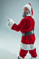 Funny guy with christmas hat posing at studio pointing to left. New Year Holiday. Christmas, x-mas, winter, gifts concept. Man wearing Santa Claus costume on gray. Copy space. Winter sales.