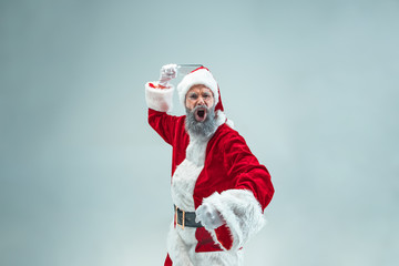 Funny aggressive guy with christmas hat posing at studio. New Year Holiday. Christmas, x-mas, winter, gifts concept. Man wearing Santa Claus costume on gray. Copy space. Winter sales.