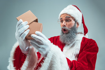 Funny guy with christmas hat posing at studio with gift. New Year Holiday. Christmas, x-mas, winter, gifts concept. Man wearing Santa Claus costume on gray. Copy space. Winter sales.