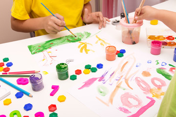 Children paint with gouache, paints , pencils. Mobile and entertainment Board games for children.Ceramic dishes in working process. Creating color patterns.