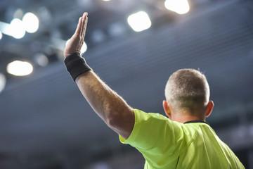 handball referee with raice hand