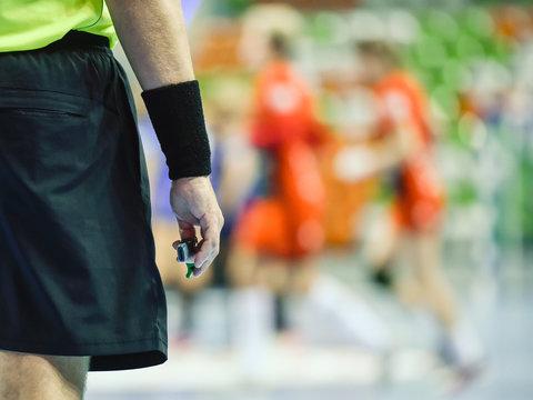 handball referee hand with whistle