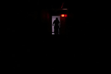 A person walks down a dark hallway in a hotel lobby that has lost its power as Hurricane Florence comes ashore on Wilmington
