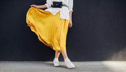 Cropped body shot of attractive woman in beautiful yellow skirt. Caucasian female fashion model standing over gray wall background outdoor with copy space. Wall mural