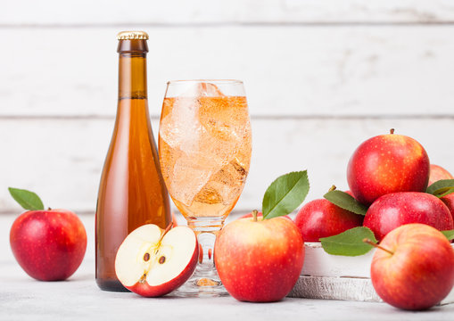 Bottle and glass of homemade organic apple cider with fresh apples in box on wooden background