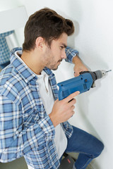 male builder drilling holes in wall at construction site