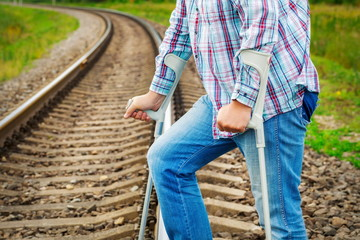 Man with crutches at railroad tracks