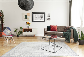 Industrial black coffee table with marble surface and a colorful patchwork chair in a living room interior with mixed style of decor.