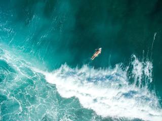 vertical shot leaky peak drone a-frame sumbawa surf ocean crystal white paddle girl