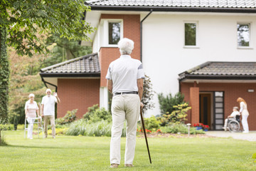 A back of a gray-haired senior man with a cane looking at his fellow mates outside of a luxury nursing home. Wall mural