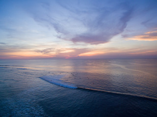 bingin beach sunset over bali surf lines clouds colors surfer indonesia