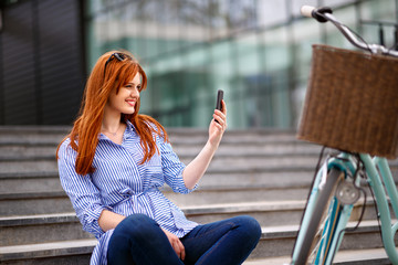 Female making selfie in town near bike