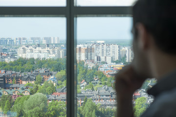 a man looks out the window at a city in the middle of the forest