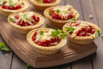 Mini pizza with salami, tomato and cheese on wooden background. Tasty appetizer, tartlet.