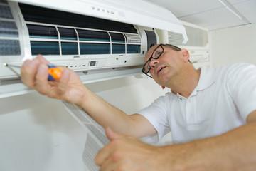 hispanic airconditioning repair man performing maintenance