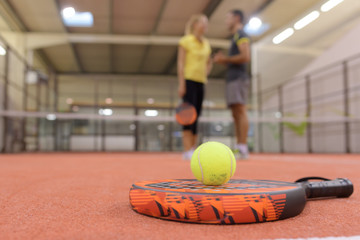tennis racket and two balls near net on indoor court