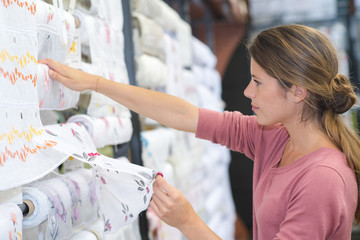 smiling woman choosing fabric in textile shop
