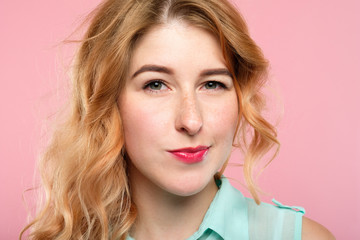 emotion face. suspicious thoughtful dubious skeptic distrustful woman. young beautiful girl portrait on pink background.