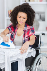 woman in a wheelchair ironing