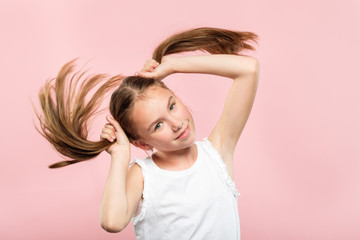 happy joyful smiling adolescent girl making pig tails from her hair. relaxed carefree lifestyle and childish behavior. young cute brown haired kid portrait on pink background.