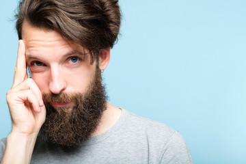 intelligence and smart ideas concept. mind games and brain power. smug confident bearded man portrait on blue background.
