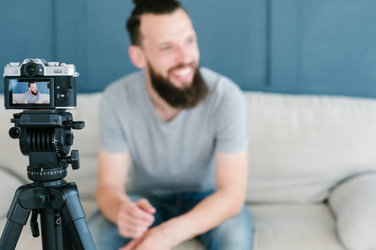 vlogging and freelance job concept. bearded man shooting video of himself using camera on tripod and creating content for social media.