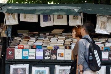 Pepople pass by antique booksellers or bouquinistes along the banks of the River Seine in Paris, France