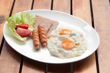 Morning breakfast, Fried egg, sausage and ham in white dish on wooden table together warm light in the morning