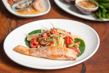 Grilled salmon steak, spicy Thai papaya salad  in white dish on wooden table background