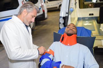 Man on ambulance stretcher wearing neck and arm brace