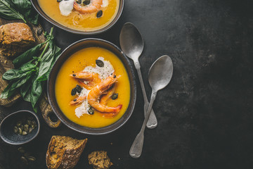 Autumn pumpkin creamy soup in bowls