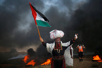 Woman holds a Palestinian flag during a protest at the Israel-Gaza border fence, east of Gaza City
