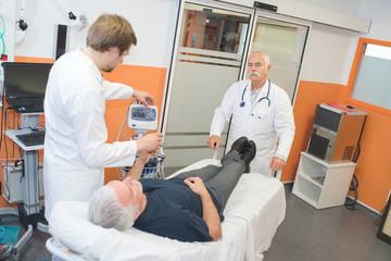 doctor measuring blood pressure of a senior patient using sphygmomanometer