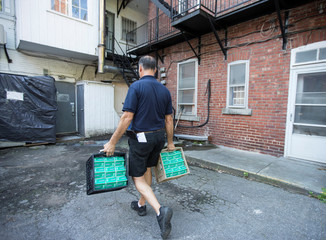 Milkman Patrick Moisan delivers milk to a small business during his rounds of home delivery service in a neighbourhood in Montreal, Quebec, Canada