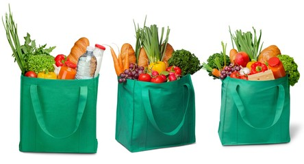Shopping bags with groceries on white