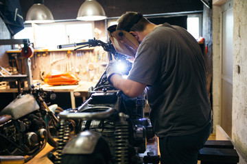 Close up shot of experienced man working in custom made motorcycle workshop.