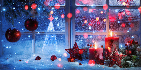 Winter Decoration With Candles Near The Snow-Covered Window. Christmas Background