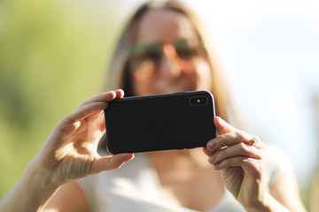 A modern phone with a camera in the hands of a young woman