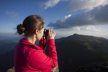 girl looking with binoculars on mountain landscape