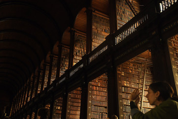 A tourist takes pictures in the Long Room of the old library that houses 200,000 of Trinity College's oldest books in Dublin