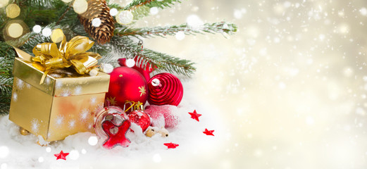 fir tree and red christmas decorations and gift box on white snow , winter banner