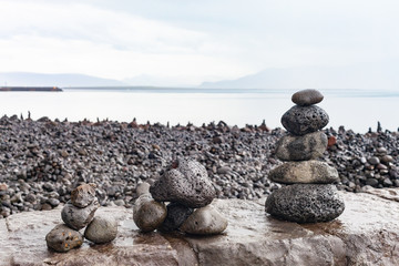 Cairns in the rain built by tourists on the shoreline of Faxafloi Bay near the Harpa Concert Hall and Conference Centre in Reykjavik, Iceland.