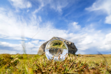 Glass orb on grass with reflection