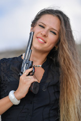 Portrait of beautiful girl with a gun on a sandy sea hill with ruins in the background