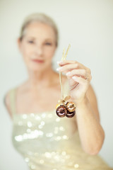 Stunning beautiful and self confident best aged woman with grey hair smiling into camera, holding Christmas decoration baubles, portrait with white background