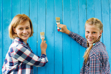 Family paints a wooden wall of blue paint. Idea of repair