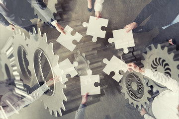 Teamwork of partners. Concept of integration and startup with puzzle pieces and gear overlay. double exposure